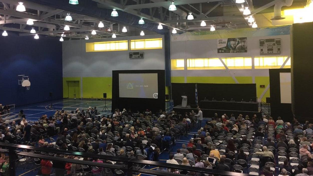 Des centaines de personnes assises dans un gymnase.