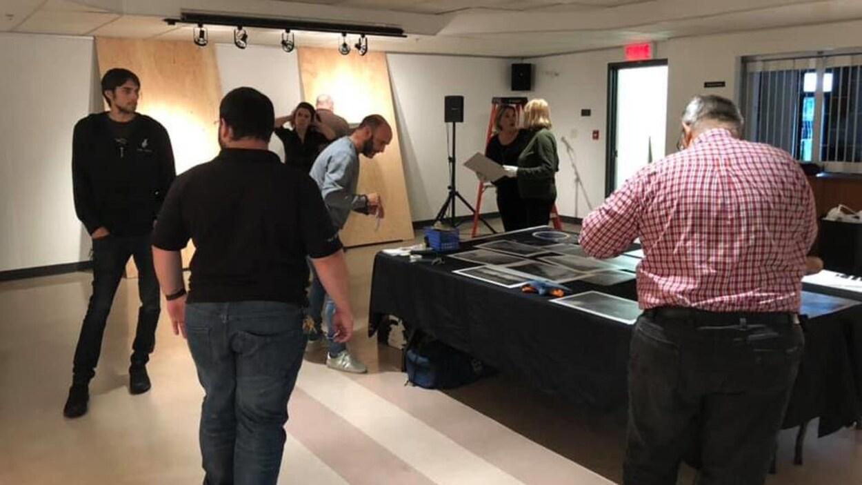 Des gens dans une salle d'exposition regardent des photos sur une table.