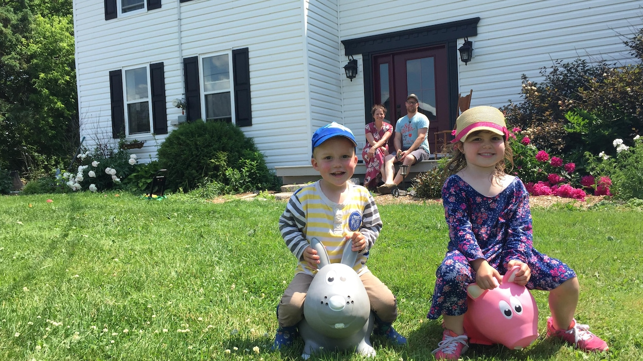 Elyse et Loïk s'amusent dehors sous le regard de leurs parents.
