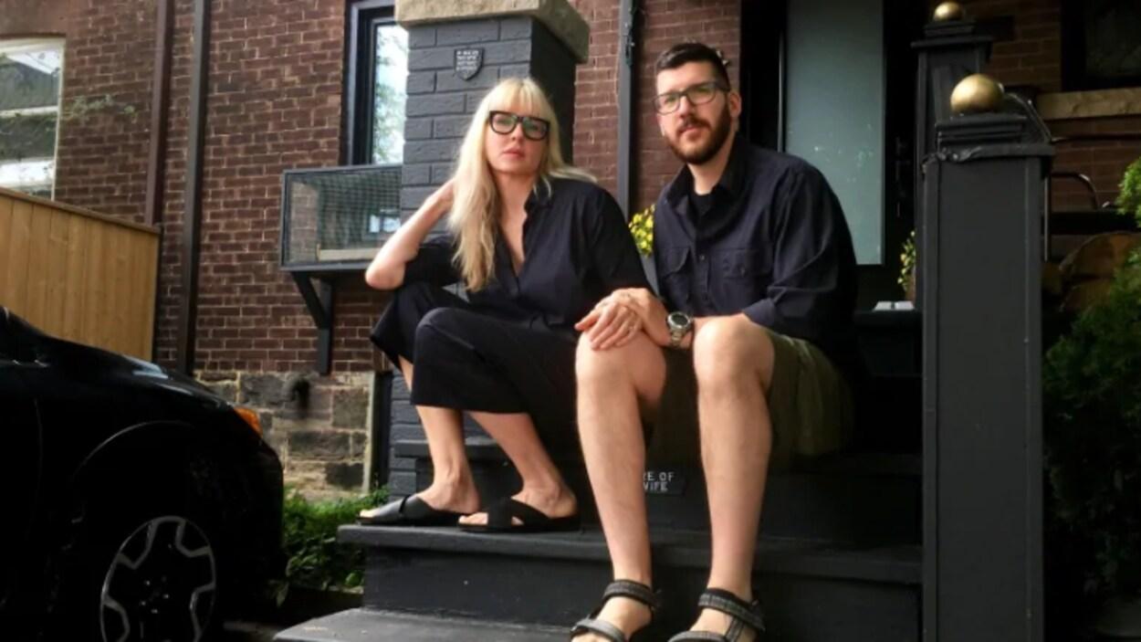 Un couple torontois assis sur les marches devant sa maison.