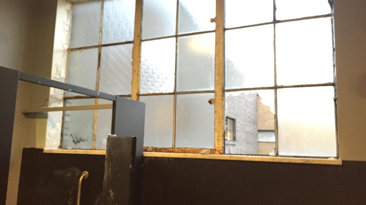 De vieilles fenêtres dans une salle de toilettes. Un des carreaux des fenêtre est brisé.