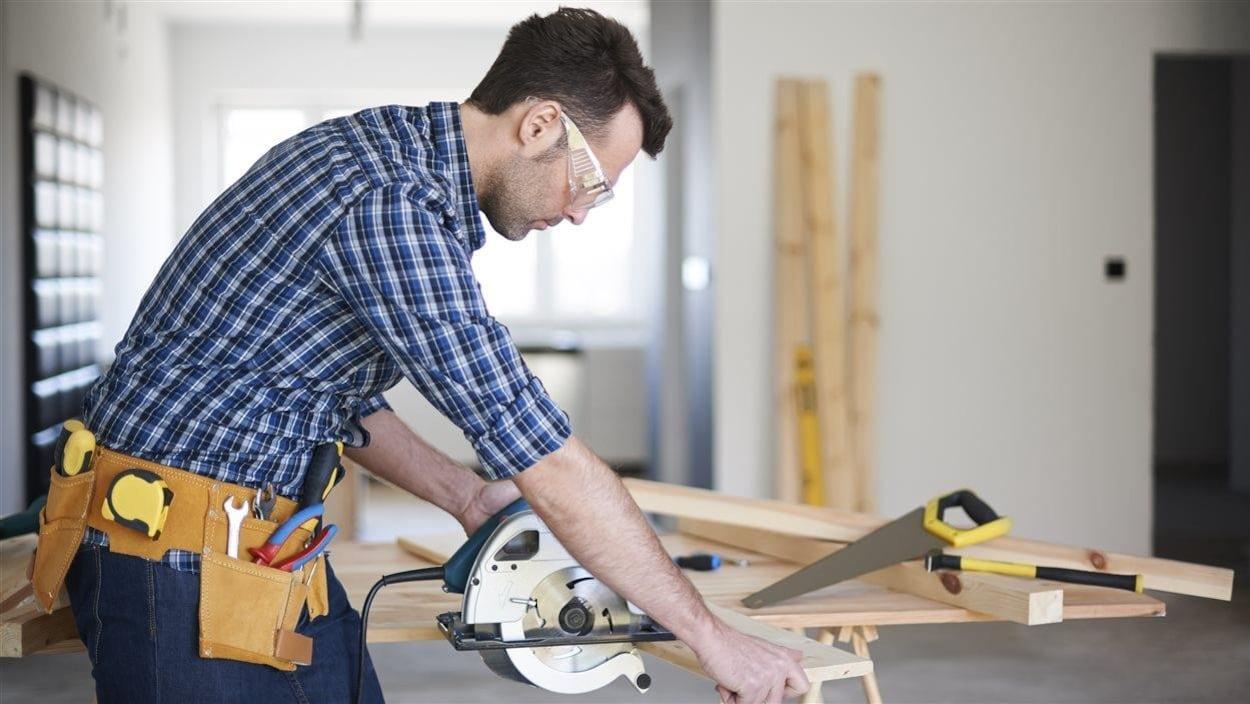Un homme coupe une planche de bois.