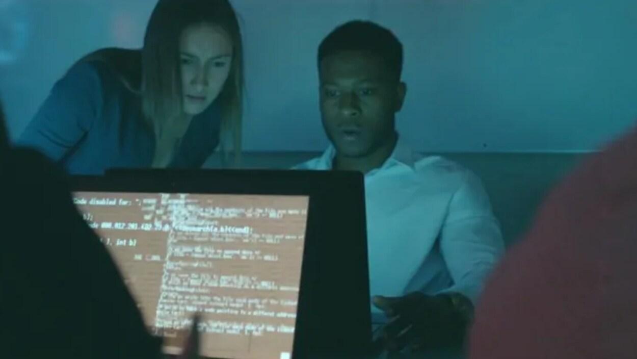 Une jeune femme, debout, et un jeune homme, assis, regardent un écran d'ordinateur, l'air concentré.