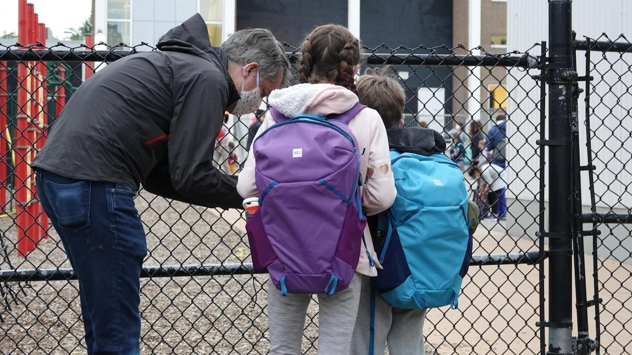 Un père portant un masque et ses deux jeunes enfants arrivent à l'école.