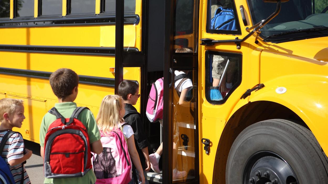 Des élèves montent à bord d'un autobus scolaire.