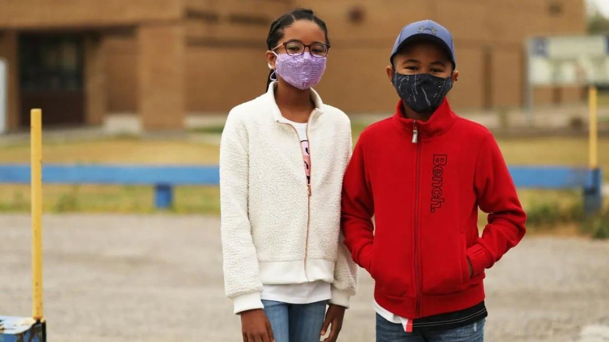 Une soeur et un frère portent le masque dans une cour d'école.