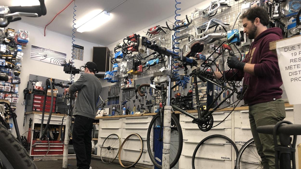 Deux personnes sont en train de réparer des vélos dans une boutique.