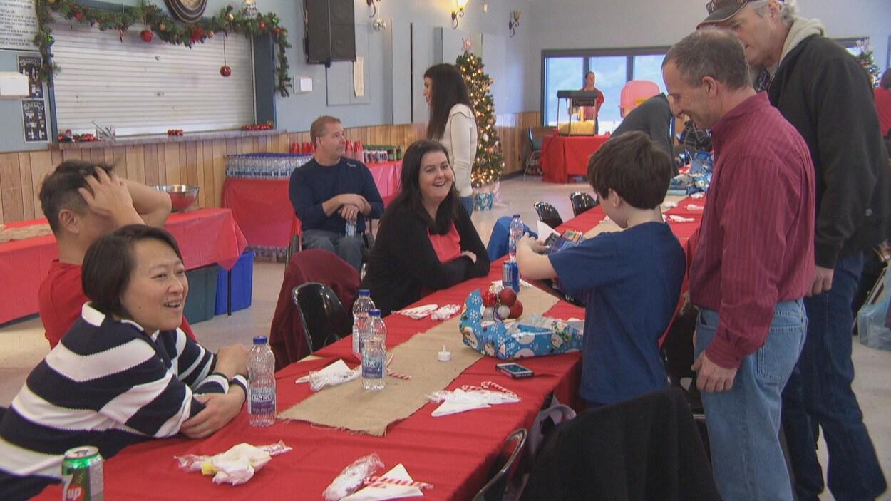 Des gens autour d'une table dans une salle décorée pour le temps des Fêtes.