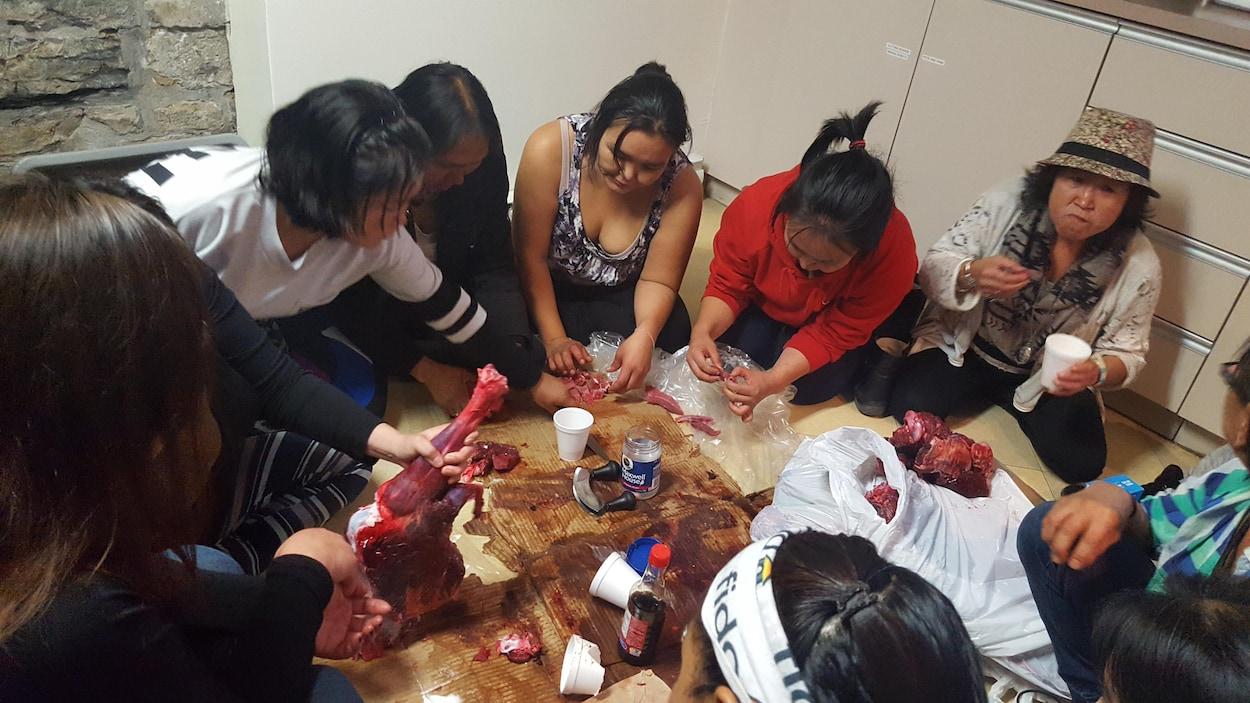 Des femmes inuites mangent, assises par terre, de la viande de caribou décongelée et crue.