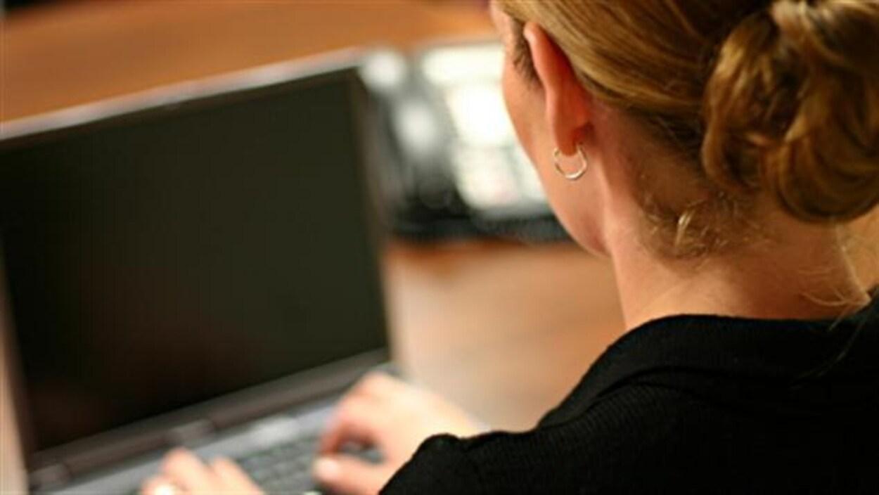 Une femme de dos devant son ordinateur