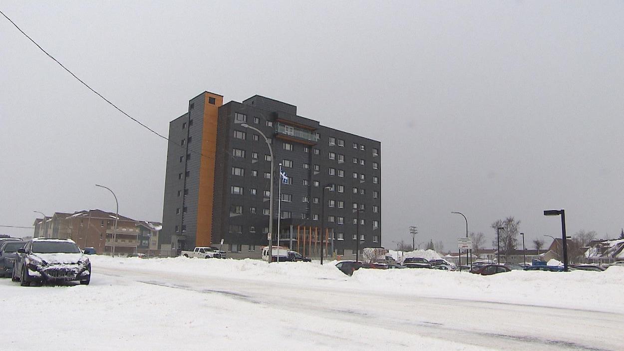 Une grande résidence de plusieurs étages dans une ville enneigée.