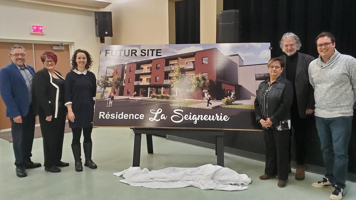 Trois hommes et trois femmes posent devant l'image d'un immeuble à logement moderne.