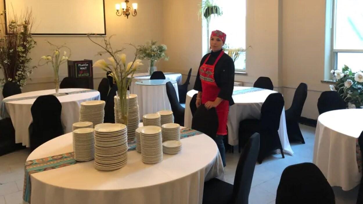 Une femme en tablier rouge debout dans une salle remplie de tables avec des assiettes.
