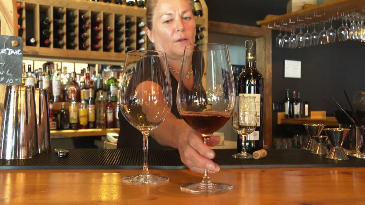 Une femme sert un verre de vin sur un bar.
