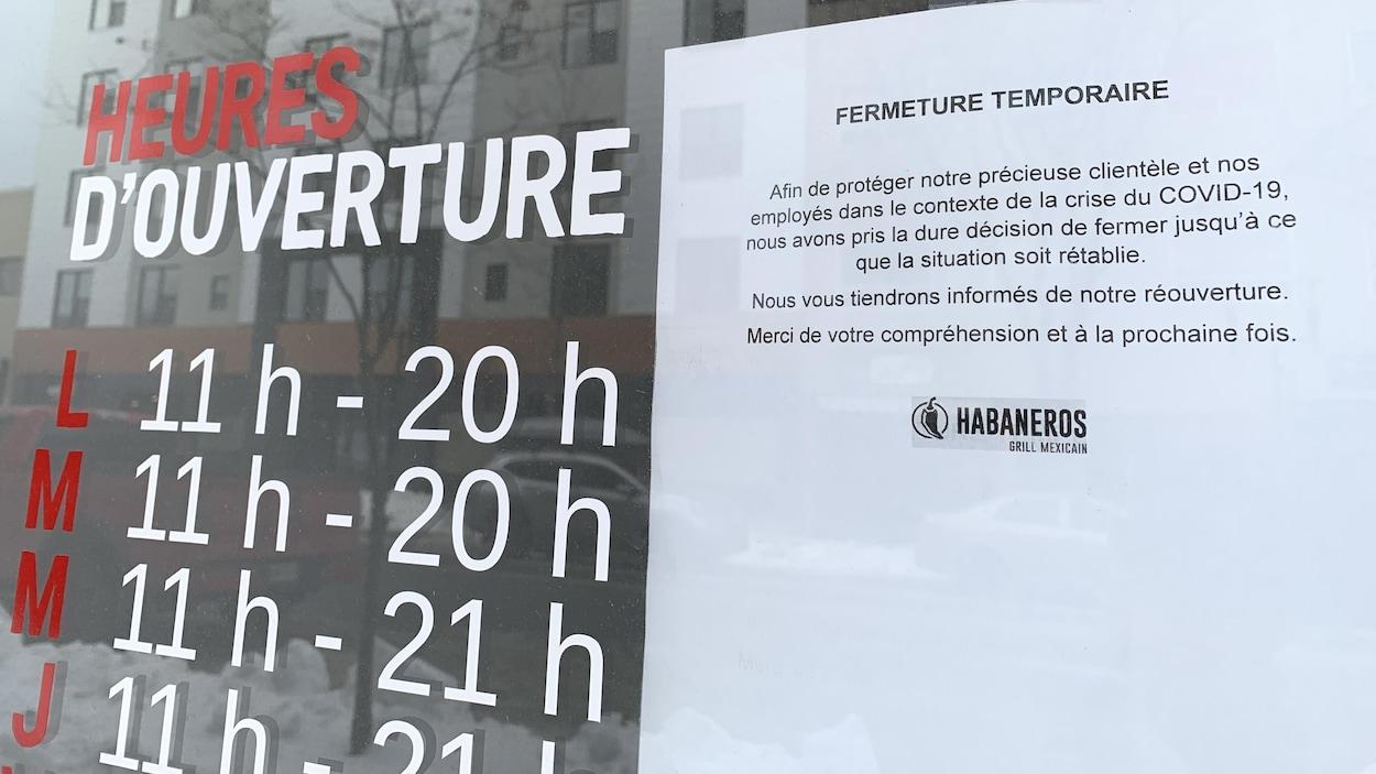 Une affiche dans la porte d'un commerce indique «fermeture temporaire».