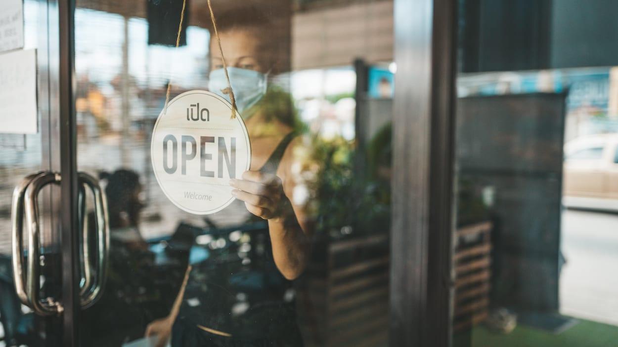 Une femme qui porte un masque tourne une affichette qui signale qu'un restaurant est ouvert.