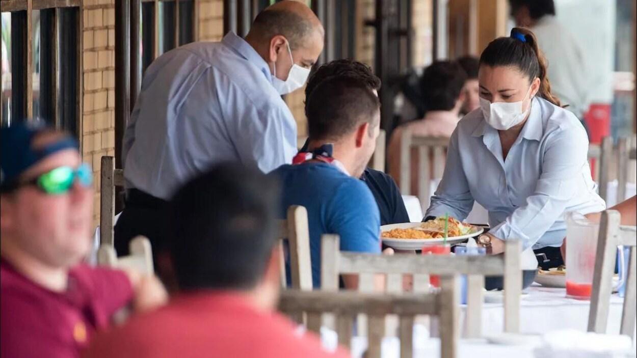 Deux serveurs portant des masques déposent des assiettes sur une table où sont attablés des clients sur une terrasse.