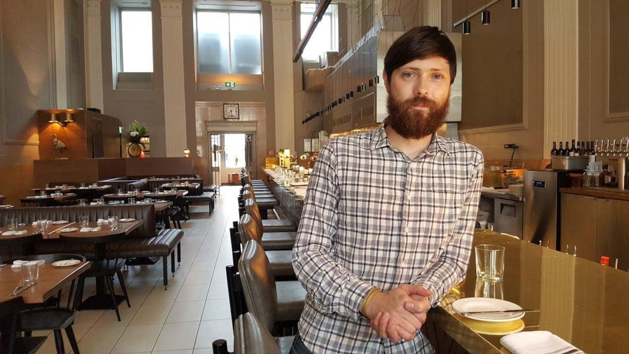 Un homme dans un restaurant, le coude posé sur une table.