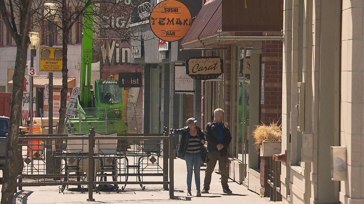 Deux passants devant le restaurant Temaki sur la rue Racine