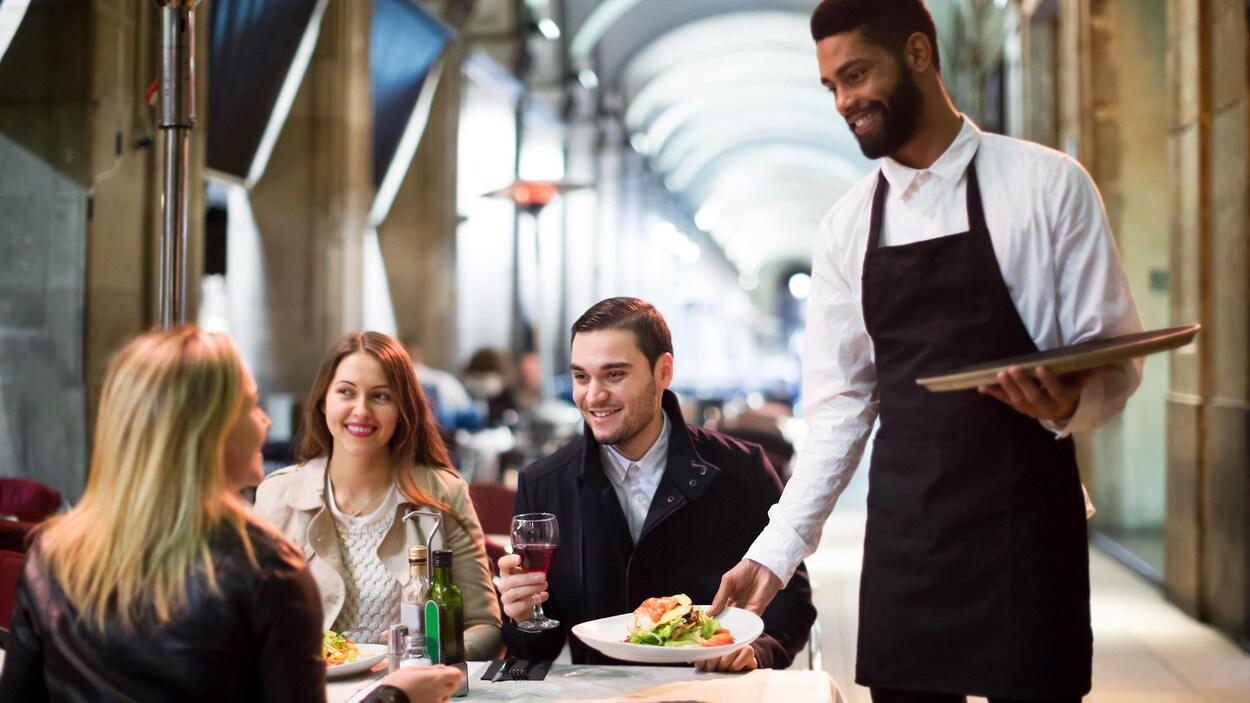 Un serveur dépose une assiette sur la table de trois clients.