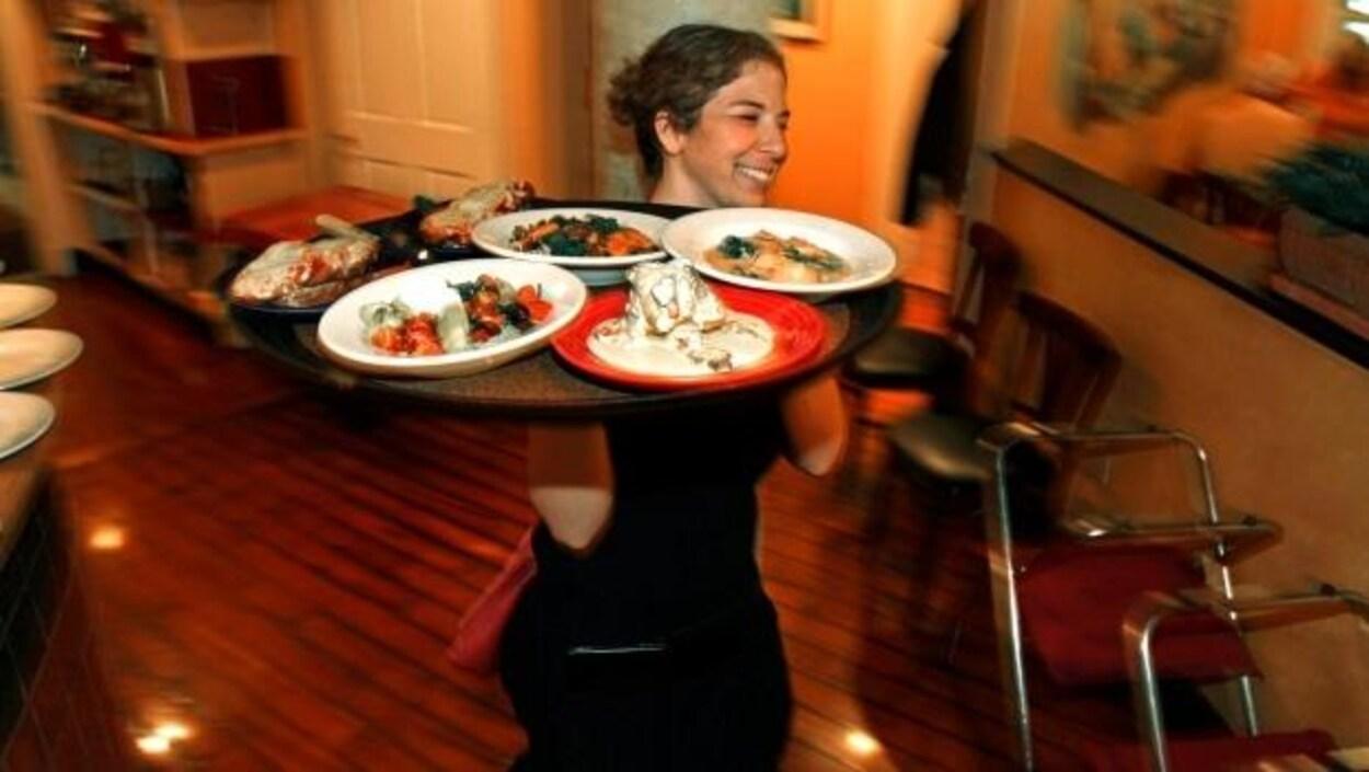 Une serveuse porte un plateau rempli d'assiettes.