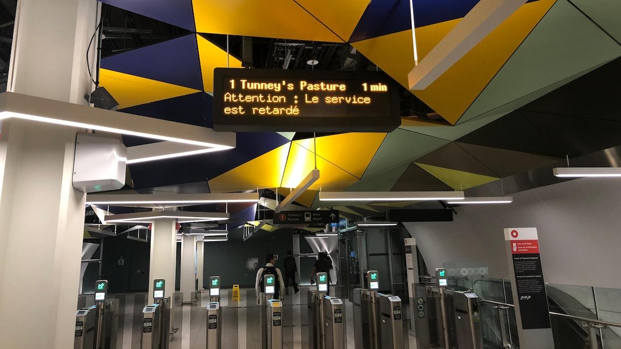 Sur le panneau, on peut lire : « Attention : Le service est retardé ».