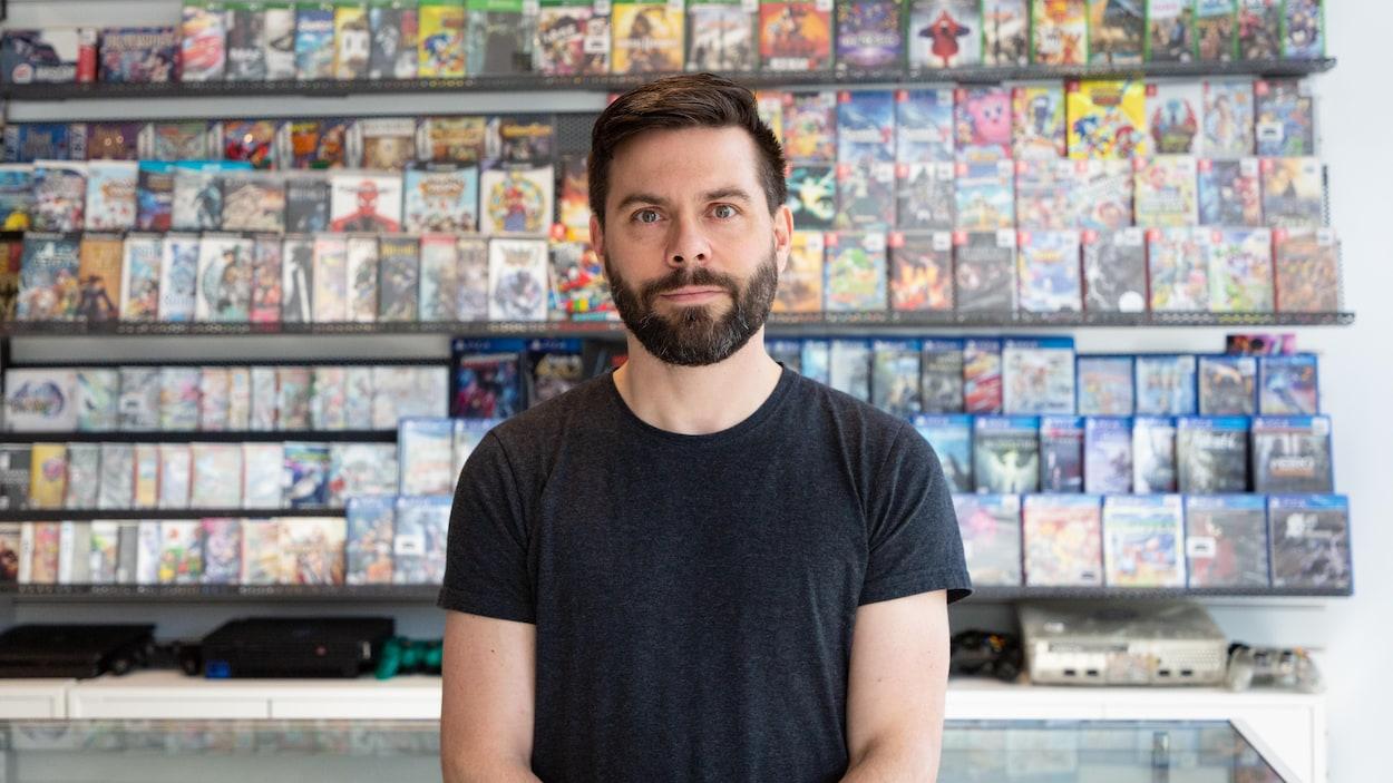 Une photo de Dominic Bourret, un homme dans la trentaine aux cheveux bruns courts portant une courte barbe, photographié devant un présentoir mural rempli d'emballages de jeux vidéo.