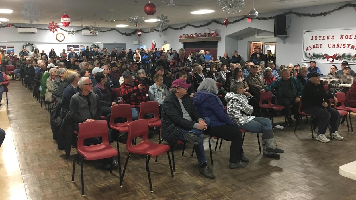 Une salle communautaire remplie de participants.