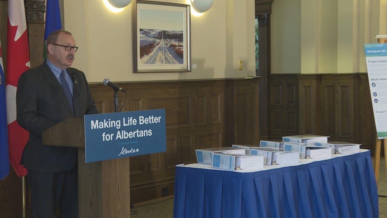 Ric McIver parle lors d'une conférence de presse. D'énormes cartables remplis de papiers sont posés sur une table.