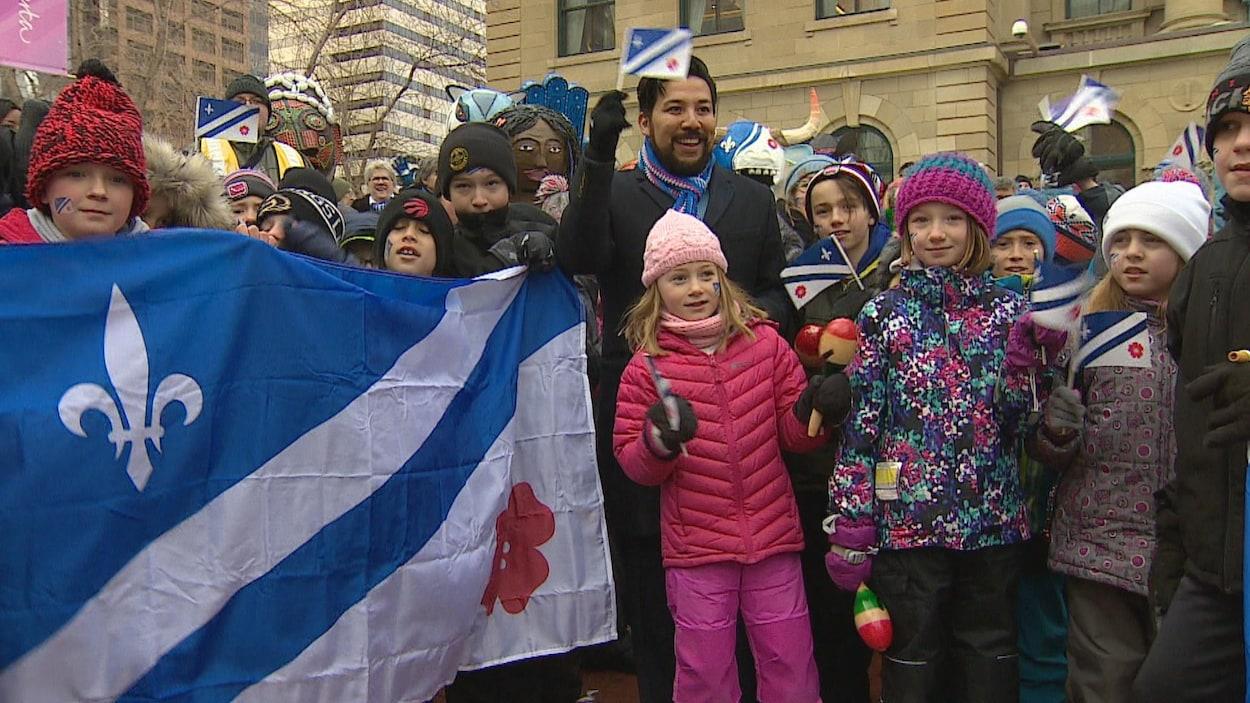 Un drapeau franco-albertain en premier plan et des enfants tenant des petits drapeaux. Les Francophones de l'Alberta ont franchi une nouvelle étape de leur reconnaissance en mars lorsque le ministre responsable du Secrétariat francophone Ricardo Miranda (au centre) a déclaré le mois de mars, Mois de la francophonie en Alberta.