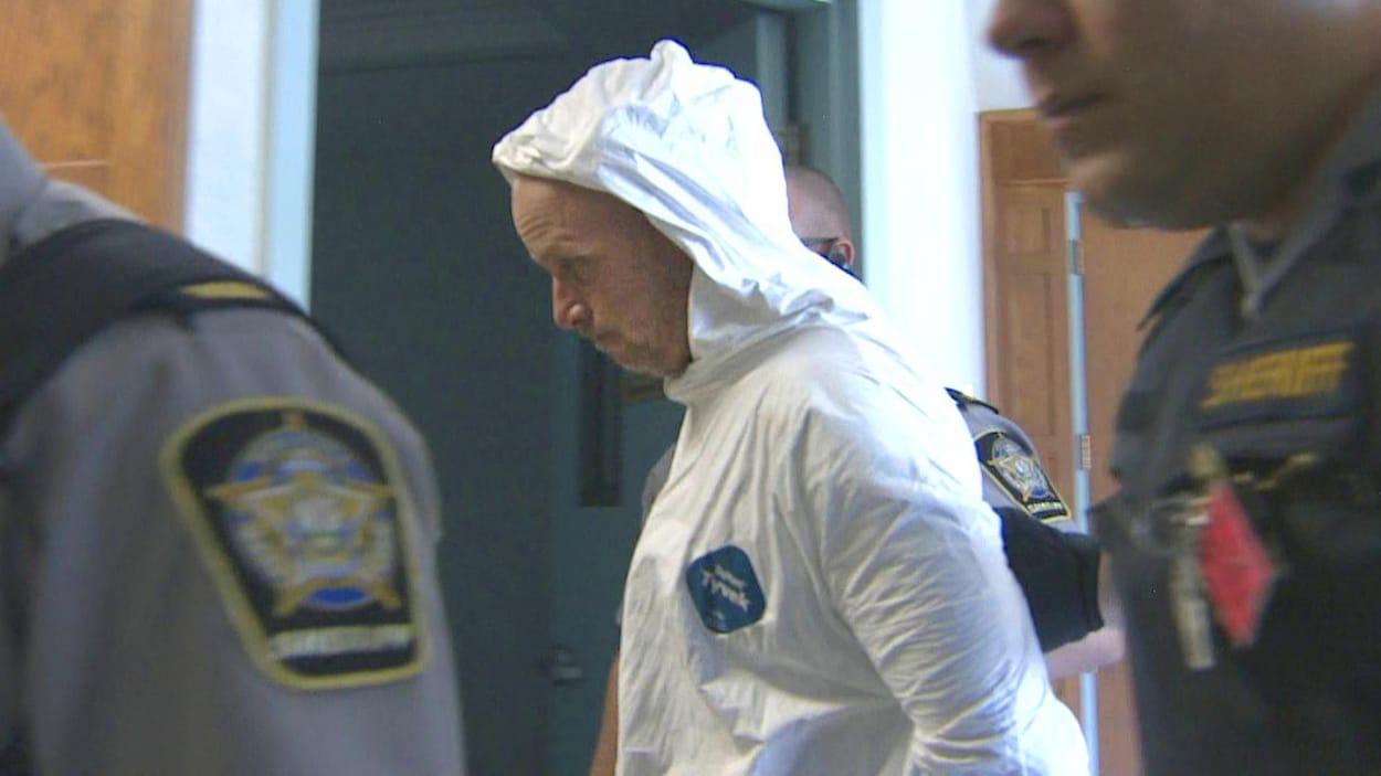 Un homme en habit blanc de prisonnier circule dans un corridor entouré de trois shérifs.