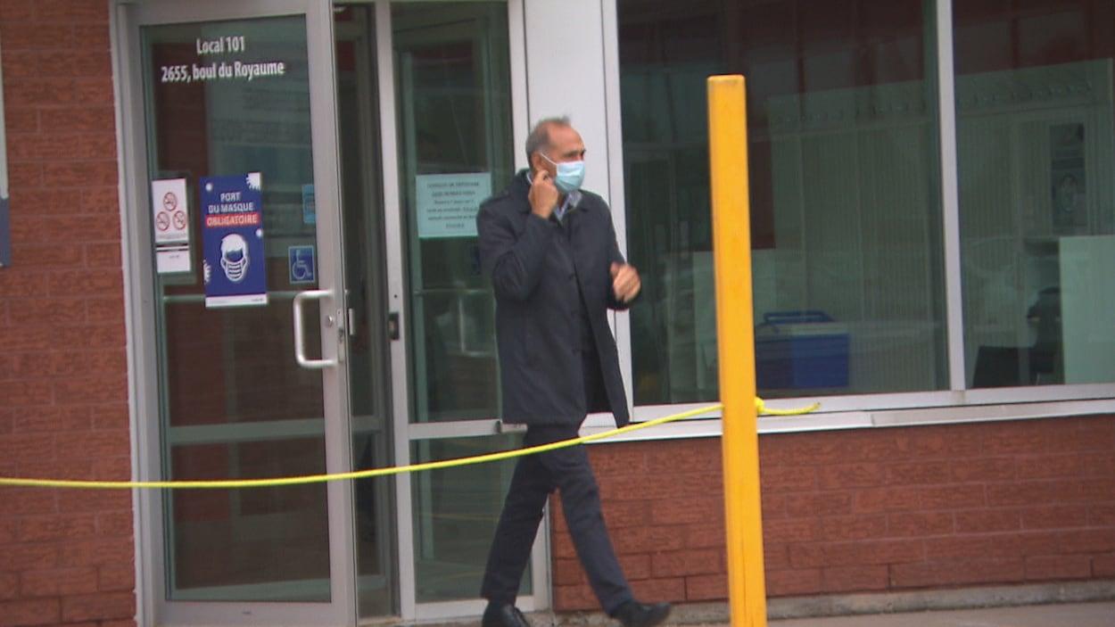 Richard Martel sortant d'une clinique de dépistage avec un masque sur le visage.
