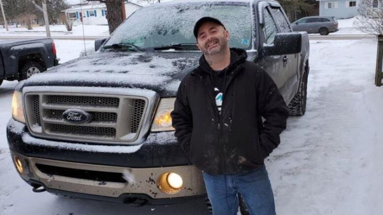 Un homme devant une camionnette.