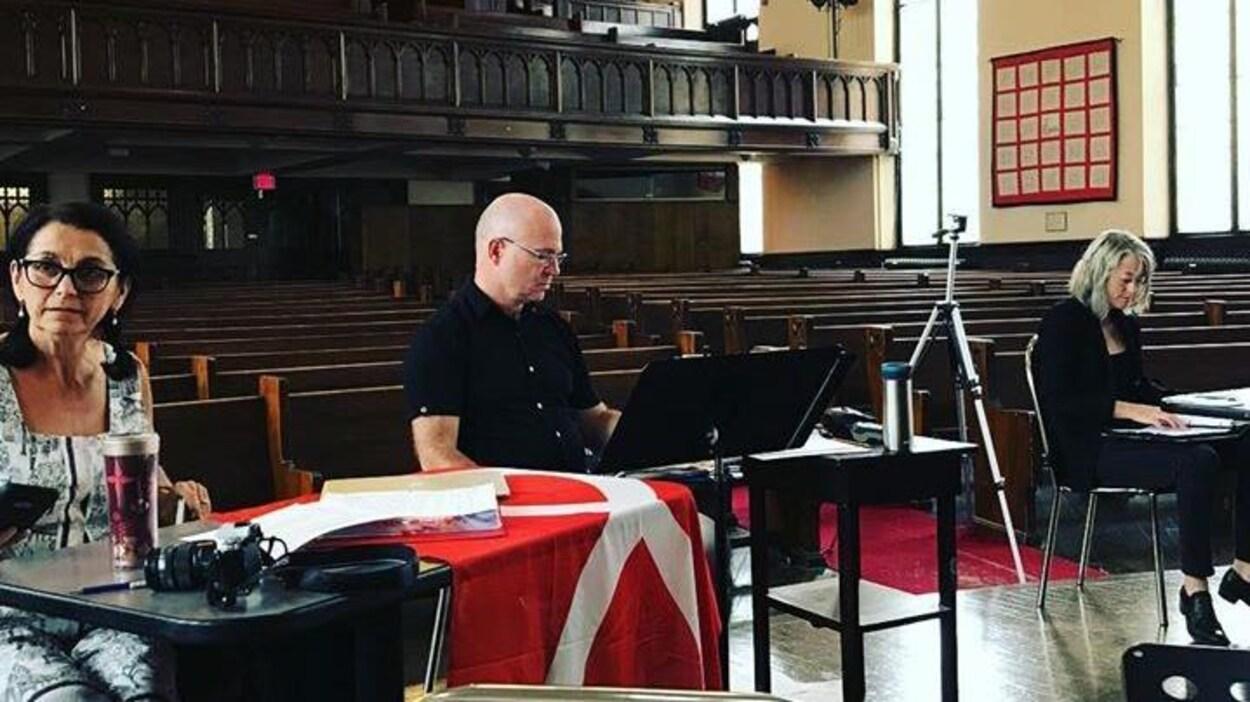 On voit trois personnes, Suzanne Steele, Neil Weisensel et Estelle Shook, assis à des tables de travail dans une église qui leur sert de lieu de travail.