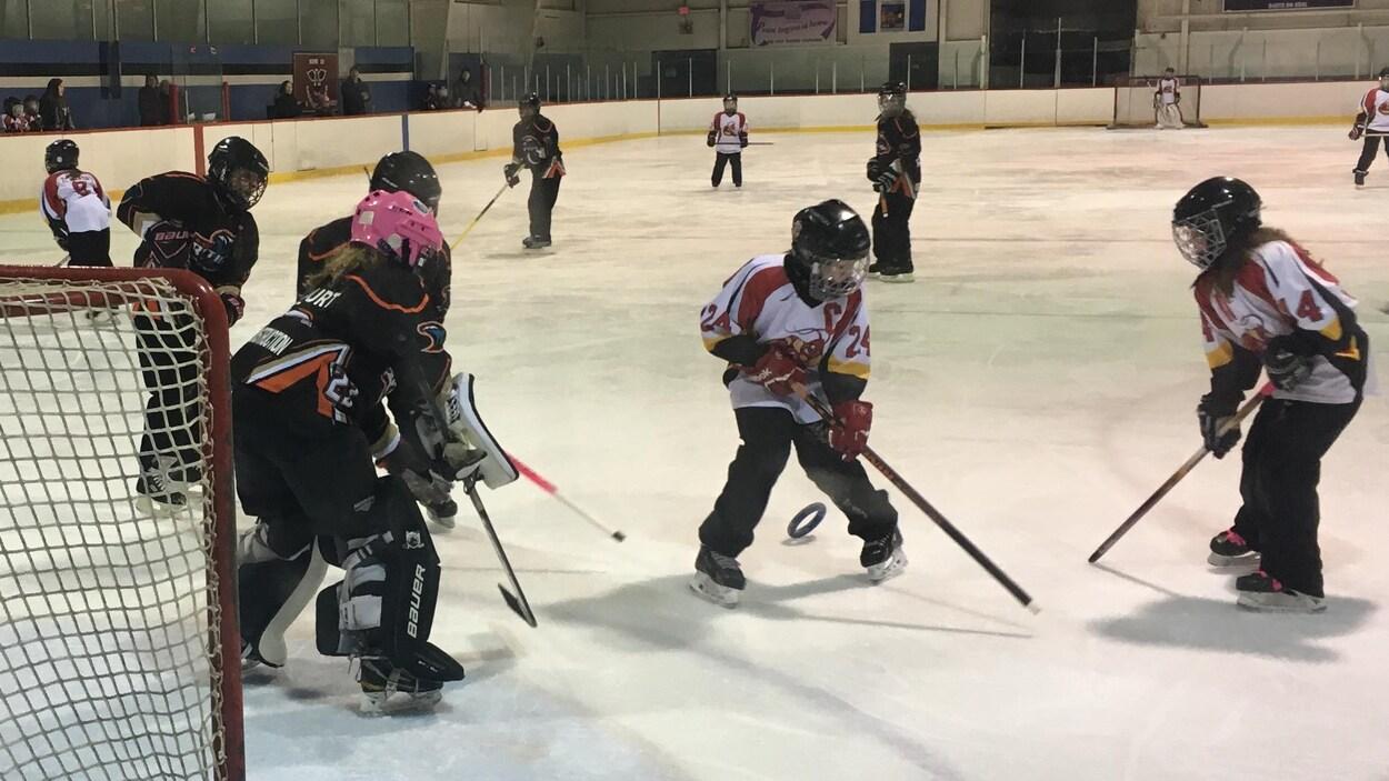 De jeunes filles sur la glace en train de jouer à la ringuette.