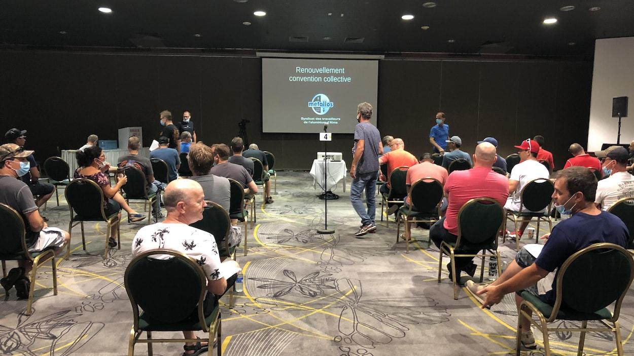 Des gens sont assis dans une salle pour voter sur leur nouvelle convention collective.