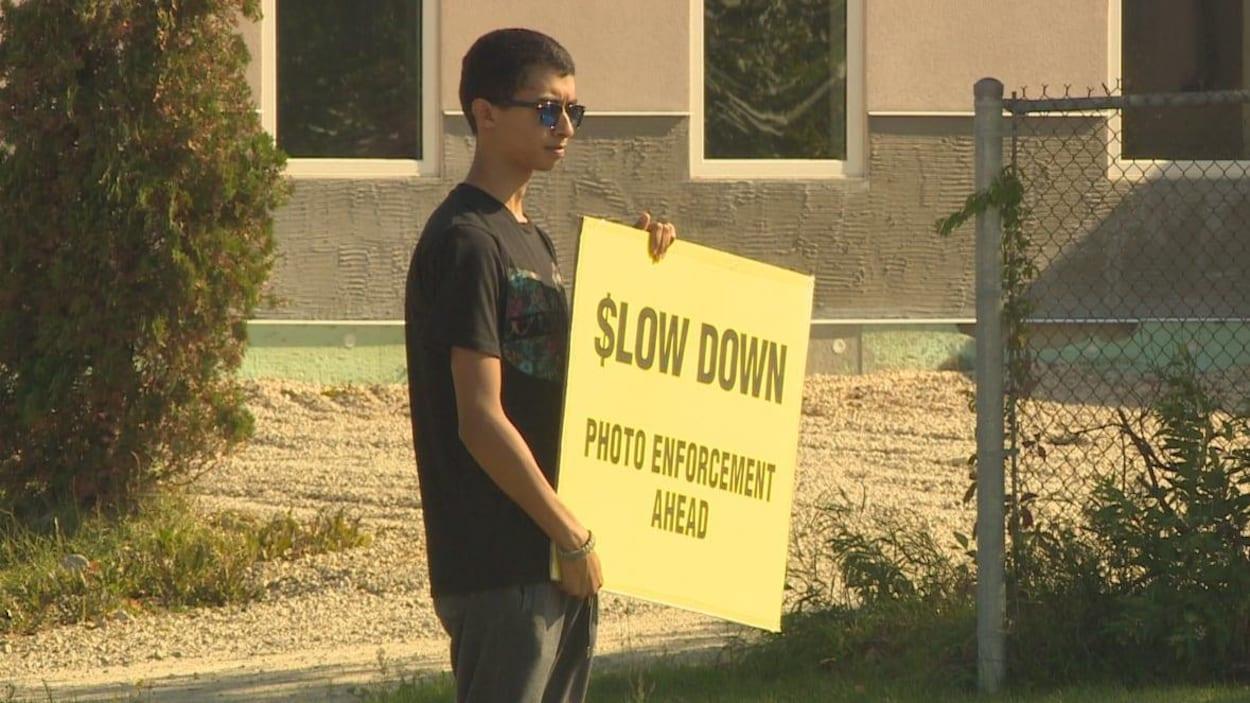 Un jeune homme tenant une affiche jaune sur laquelle on peut lire en anglais les mots : Ralentissez, radar photo devant.