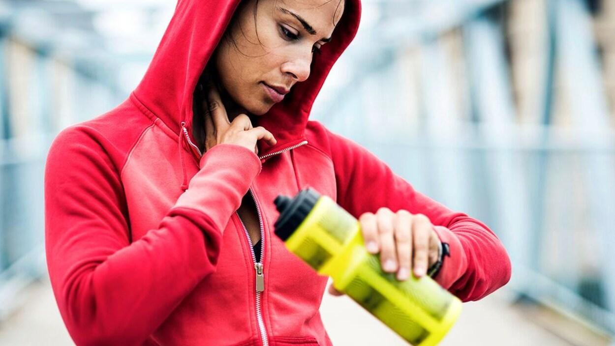 Une femme en train de faire de courir, s'arrête pour prendre son poux avec une bouteille d'eau jaune à la main.