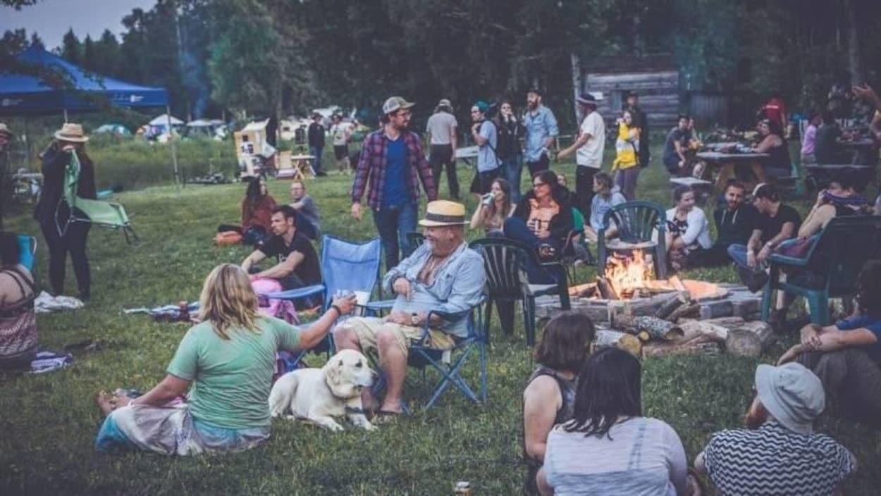 des campeurs lors du festival River and Sky, dans l'herbe avec des chaises et des feux de camp