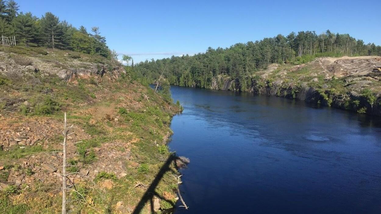 Une rivière aux rives rocheuses surplombées de conifères.