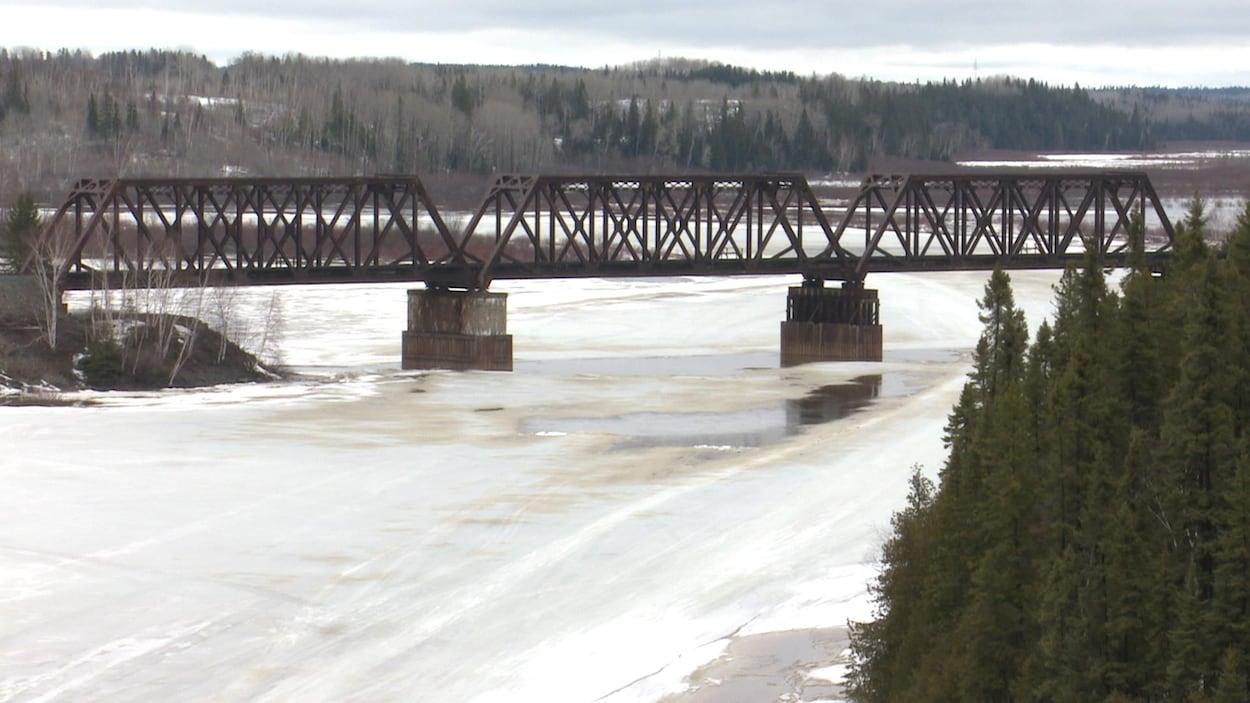 Une rivière traversée par un vieux pont ferroviaire fond au printemps.
