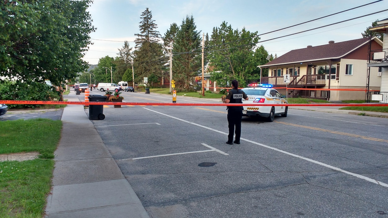 Une policière et une voiture de police dans une rue bouclée par un ruban de sécurité.