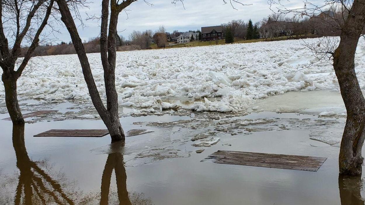 Une rivière couverte de glace avec deux tables de pique-nique englouties.