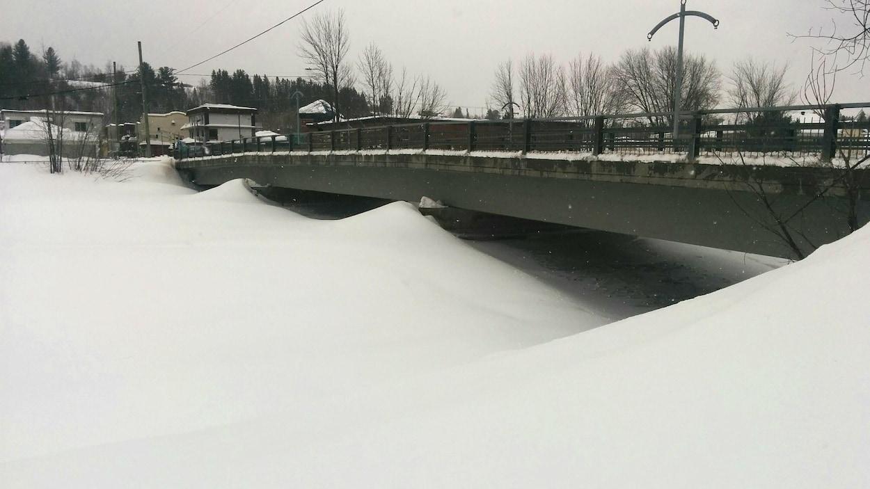La rivière Sainte-Anne photographiée en hiver. On aperçoit un pont surplombant la rivière. Cette dernière est entièrement recouverte de neige.