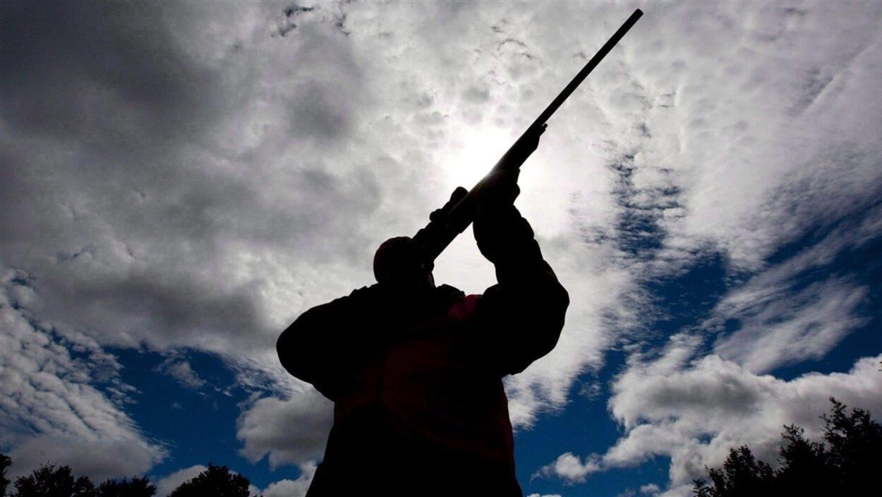 Une personne tient une arme d'épaule utilisée pour la chasse