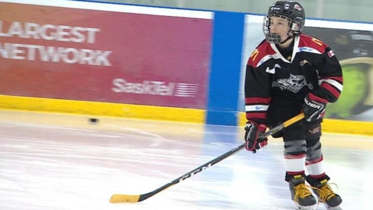 Roan Dahlen joue au hockey avec des lacets jaunes et la palette de son bâton de hockey tapissé de ruban adhésif jaune.