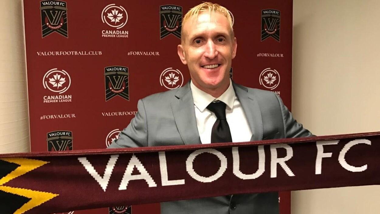 Un homme debout tient une écharpe du Valour FC.