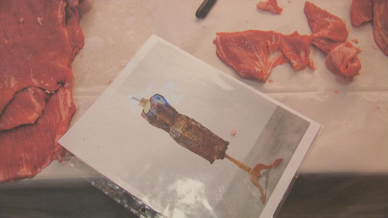 Une photo de robe où on voit une robe en viande séchée est déposée sur une table de boucher. La robe est entourée de morceaux de boeuf. On y voit le manche d'un couteau.