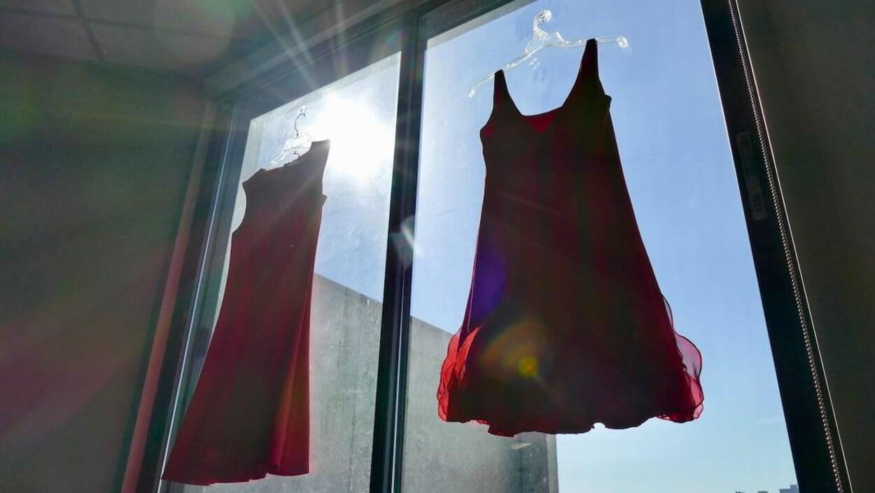 Deux robes rouges accrochées devant une fenêtre.