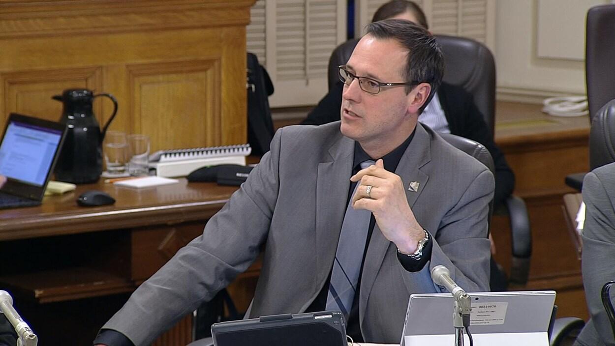 Jean-François Roberge assis devant un micro et des écrans de tablettes.